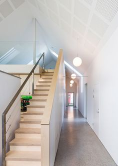 A long corridor on one side of this home leads to a series of additional rooms and links the extension to the original building, while stairs lead up to a mezzanine level.