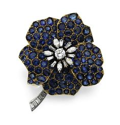 SAPPHIRE AND DIAMOND FLOWER BROOCH, CARTIER.  Set in the center with a round diamond weighing approximately .55 carat, surrounded by 5 marquise-shaped and 13 baguette diamonds weighing approximately 1.35 carats, the petals studded with round and oval-shaped sapphires, mounted in 18 karat gold and platinum, signed Cartier.