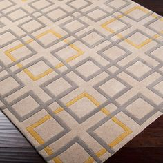 Geometric Simplicity Hand-Tufted RugA crisp, modern geometric pattern in fashion forward colors, the neutral beige ground is overlaid in a gray gridwork accented by pops of yellow squares. Hand carved and tufted 100% New Zealand wool