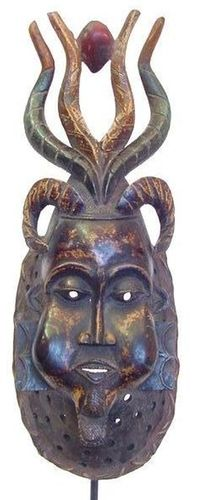 Africa |  Guro Mask | Ivory Coast | A carved wooden and painted mask with three sets of antelope horns and red seed detail.