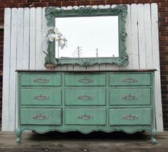 Nine drawer French Provincial Dresser in Soft Jade with a floral stained top. The top is super glossy and oh so smooth! The flowers have been shaded in with stain and shows off the pretty wood-grain. The interior has been painted in off white and the original pulls in Aged Nickel. Modern Vintage