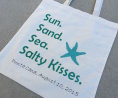 """This cotton tote bag is 15"""" by 16"""" and has """"Sun. Sand. Sea. Salty kisses."""" In aqua glitter lettering and includes custom lettering which can be location, names, dates, or whatever you would like! Plea"""