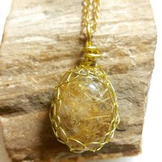 Gold Viking Knit wrapped rutilated quartz crystal pendant on gold colored chain.