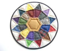 Colorful quilted table topper or candle mat for rustic country home decor.  This quilted table topper or candle mat measures 11 1/2 inches in diameter. I have hand pieced from many colorful calico cotton and homespun fabrics. The center fabric is a solid deep gold colored cotton. The backing is a multicolor homespun check. A black cotton muslin is used for the binding.  It is layered with high loft polyester batting then hand quilted with black quilting thread.  Laundered once after…