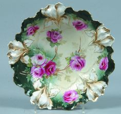 "RS Prussia Signed Bowl, 8.5""d.; Mold 25, Iris; FD: hand painted dark and light pink 3 rose cluster with leaves, 2 more on branches. 4additional rosesin border on a green band between white Iris. Iris witj gold outling"