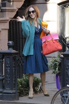 Sarah Jessica Parker waves hello as she leaves her NYC townhouse with her handbag and a bottle of Veuve Clicquot champagne!