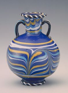 Core-formed glass vessels with patterned decoration were fashioned as containers for costly perfumed ointments, scented oils, and cosmetics.  The vessel shapes generally imitated those of containers made of beautifully veined stone or decorated pottery, industries of great antiquity and sophistication in ancient Egypt.