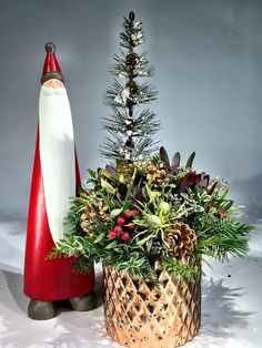 Christmas centrepiece of pine, cedar, hypericum berries, leucadendron, berzillia berries, comes in a gold mercury glass vase.