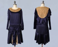 1920s dress in stunning blue-purple silk satin. Classic flapper silhouette with loose, boxy fit and dropped waist. Long sleeves with snaps at wrists. Intricate antique ecru lace yoke front and back. Bias cut cape back. Wide sash at dropped waist, accented by a big floppy bow with dangling ends in center. Subtle gathers at the hips. Skirt is voluminous and fluttery, with bias cut and layered front. The front pieces are backed in cream satin that just peeks out. Wonderful effect. Measurements…
