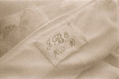 """A piece of the mother's wedding dress (something old) embroidered with brides initials and wedding date in baby blue (""""something blue"""")."""