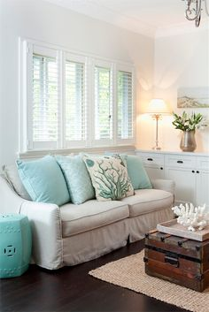Beachy/coastal style in a living/family room: love, love, love the built in credenza/console. Love using the garden stool as a side table (because it is, after all, turquoise), and coastal accents. (The coral, though, should always be faux; leave the real stuff in the sea.) Nice space.  (House of Turquoise.)