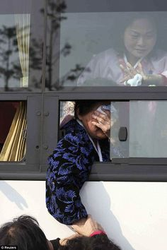 Tearful: South Koreans hold hands with their North Korean family members (pictured inside bus) before they are separated again