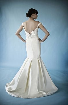 Caroline DeVillo - Breanna. Silk Mikado mermaid gown featuring box pleats at chapel train, portrait neckline and silk satin bow detail at the open back