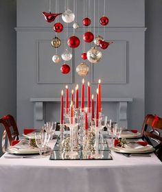 Fun tablescape with ornaments hanging centered above the table. Christmas red candles with various crystal candle holders on mirrored panels create a ...