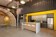 Natural wood, white, and a big pop of yellow in this warehouse-style office space. Love the backsplash in the kitchen. Cunningham Group Architecture Office