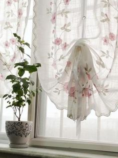 Sheer fabric with a soft floral print is gathered up in the center letting in the light while providing both pattern and privacy.