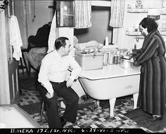 """The Baiera family in the kitchen of their """"classic tenement -- note transom over kitchen bathtub"""" at 17 East 1st Street, near 2nd Avenue, on the Lower East Side of Manhattan (now called the East Village), June 24, 1940."""
