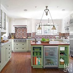 The cool green island offsets the warm tones on the handmade backsplash tiles. Open storage, a beverage fridge, and an additional sink help this island work hard and look great./