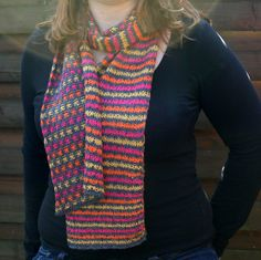 This is a pattern for a reversible scarf, with stripes on one side and multicolored squares on the other one. This effect is made working only one color at a time, with the use of slipped stitches