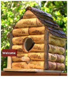 Birdhouse, wine corks, tree bark, or cedar planks (the damaged ones are VERY ceahp at home improvement or lumber yards) , sticks fromt he yard, craft store birdhouse kit (the cheap ones, Dollar Store has them too).... just split and use some good glue... seal and hang outside.... very whimsical, DIY crat idea, if you split the corks, this would work for boy scouts, or younger children.... recycle, upcycle green craft idea!