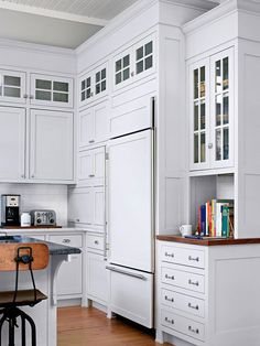 Aging Gracefully: Cabinetry Cabinet panels provide creative cover-ups, concealing the built-in refrigerator (shown here) and dishwasher. Cabinetry to the left of the fridge conceals a microwave and other small appliances. Furniture-style feet at the base of the cabinets recall kitchens of the pas