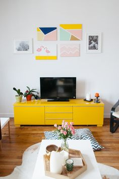 A minimal space can still be bright and fun. Found among these white walls and plenty of simple, white furniture you find this bold, bright, yellow TV entertainment cabinet with equally fun art on the wall above.