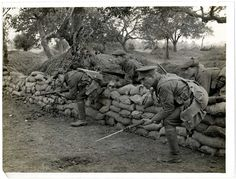 """WWI: """"We can see a small group of soldiers coming out of a trench, over the protective sandbag wall. They have their bayonets fixed, ready for an attack. It is not clear whether this is a staged photo or not. The work of official photographer Charles Hilton DeWitt form an important record, their documentary value must be assessed with caution. Girdwood's was an explicitly propagandist role on behalf of the war effort in general and the India Office in particular."""" - The British Library."""