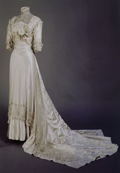 Wedding dress, Meynier, Paris, early 1908. Ivory silk satin covered with matching net in piped pattern. Applied silk rouleau in swooping, elongated Art Nouveau scrolls. Square-ended train, artificial orange blossom.