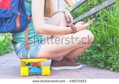 Close-up of skateboarder girl sitting on skateboard outdoor and using mobile phone. Dressed in shorts, wearing a sport backpack. Skatebord at city street. Tenager. Skateboarding at Summer. Schoolgirl