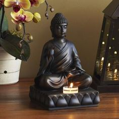 """BUDDHA CANDLE HOLDER 4.9 out of 5 Read all 21 reviews  Write a review Item #:  P9168   Buddha sits with his right hand raised, palm facing out, fingers upright and joined. This symbolizes peace and protection. Resin with bronze finish. 9""""h, 6""""w, 6"""" depth"""