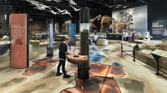 map on floor, floating displays off columns, interesting use of space; neat cases to the rights and Plexiglas for water is display behind them. Also used space above people for hanging specimens from ceiling.   Natural History Museum of Utah at Rio Tinto Center - Graphis