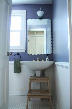 Small spaces. Scallop border mirror. Love the dark and calming blue and retro hardware.