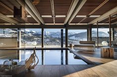 Expansive indoor pool with jet streams and a view of the snow-covered Alps - Decoist