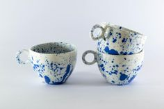 Beautiful blue speckled mugs by English artist Anna Jones. Annamakes one-off functional ceramic pieces in stoneware, usinghand building and press moulding techniques.    The glazes are applied by various methods, often by flicking glaze from a small brush to achievea splattered effect.The work is inspired by simplicity of form from ceramic cups and bowls of the Chinese Tang Dynasty (618-907) and marbledsurface decoration from contemporary American enamel tableware. Measurements: D: 9 x…
