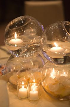 Stacked glass orbs with floating candles and petals #sarahkhaneventstyling #centerpiece #roses #candlelight #centerpiece