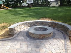 Natural Stone sitting wall with bluestone cap surrounds a fire pit and paver patio by Bahler Brothers