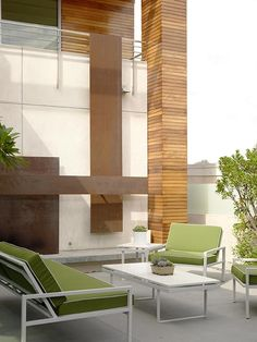 This home's modern architecture makes the perfect backdrop for the outdoor living space.  The geometric shapes of the wood clad columns and brown rectangular steel panels are mirrored in the simple shapes of the patio furniture.  The green fabric on the chairs and sofa perfectly matches the small potted trees and shrubs.  By Kenneth Brown Design.