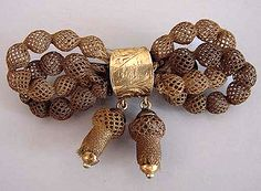 "A Victorian table worked open ""beads"" hair bow pin with acorn drops. The knot of the bow is gold tone inscribed with the name ""Lizzie."" It measures 2-1/2"" by 1-1/4"".  [Photo courtesy of Morning Glory Antiques and Jewelry]"