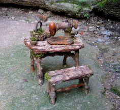 A tiny vintage style sewing machine of acorn parts, magnolia stem and chestnut hull is perched on a bark table top amid acorn baskets and a miniature tea cup. The seamstress bench is of bark and twigs and measures centimeters long x cm. high c Fairy Garden Furniture, Fairy Garden Houses, Twig Furniture, Fairies Garden, Gnome Garden, Furniture Legs, Garden Gate, Barbie Furniture, Furniture Design