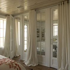 beautiful french doors dividing bathroom from bedroom ... pool on the floor draperies.