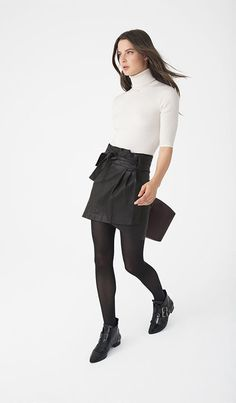 French girl style: white turtleneck with a leather wrap skirt and black ankle boots