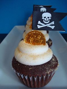 Client wanted to save a little money, so we used paper flags and gold foiled coins for these pirate cupcakes. They are topped with crushed graham crackers for the look of sand!