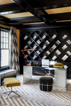 Spazio Rosso, Inc. choose a dijon paint color for the walls and yellow raffia wallpaper for the ceiling in this contemporary study. The built-in shelves were redesigned in a diagonal pattern to create a unique geometry, which the area rug and drapery fabric were chosen to enhance. The desk is composed of two layers of glass, the top being black, underneath being white.