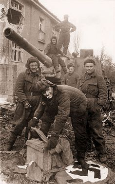 Soviet SU-152 crew wiping feet with a Nazi flag.