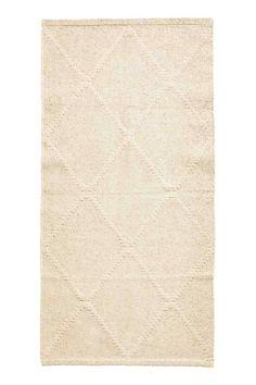 Tapis jacquard en coton: Tapis rectangulaire en coton tissé à motif jacquard.