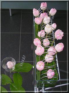 Tulpen met spiraal in een rechthoekig, glazen recipiënt met appelblad