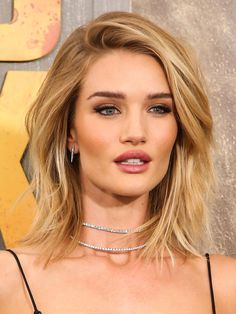 Rosie Huntington-Whiteley has tousled beach hair, bronzed makeup and a delicate silver choker necklace.