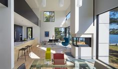 white walls, pops of color, pennisula fireplace (put between dining and sunroom ?), window walls, black trim around windows and glass table House on Solitude Creek by Robert Gurney Architects Maryland, Spacious Living Room, Living Spaces, Living Rooms, Home Office, Faia, Bright Homes, Modern Fireplace, Small Places