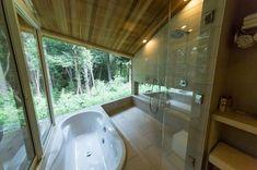ガラス張りの開放的なバスルーム。雑木林に囲まれた清々しい雰囲気に、疲れが癒される。