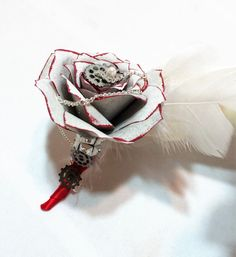 Silver and red Steampunk/Rockabilly themed boutonniere using small handmade paper filter Roses with cogs, chains, a pearl center and silver feathers . The stems are wrapped in red satin ribbon. Flowers are handmade using sturdy coffee filter paper. Each flower petal is hand cut, painted and individually hung to dry so colors dont fade. Flowers are then assembled petal by petal, shaped and curled to create the perfect flower that will last a lifetime.  Sizes are approximate • Small pin o...